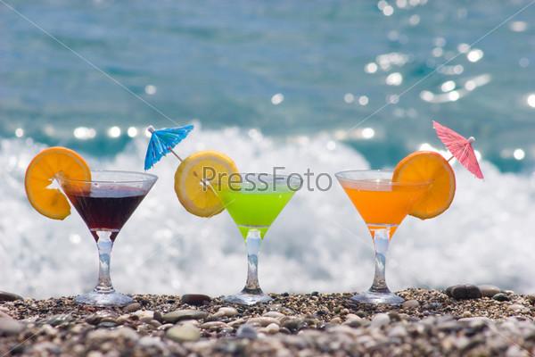 Три ярких коктейля стоят на гальке на фоне моря