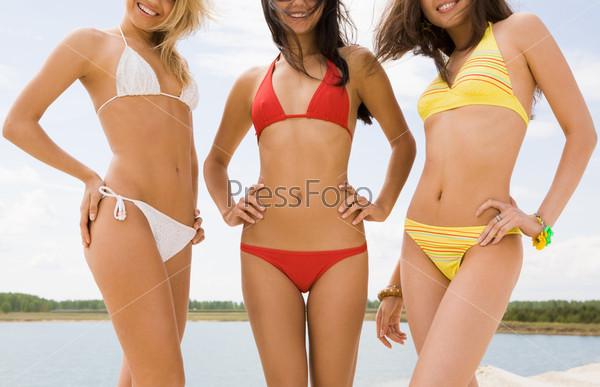 Стройные женские тела в купальниках на фоне природы
