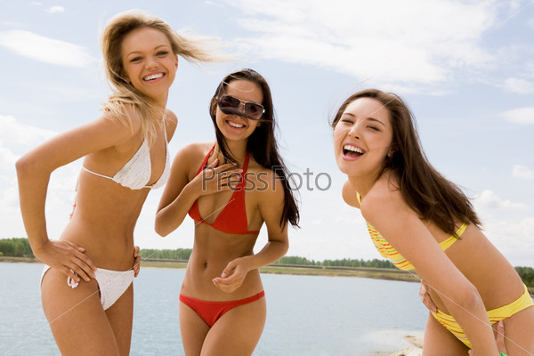 Шикарные девушки в купальниках смеются на фоне озера