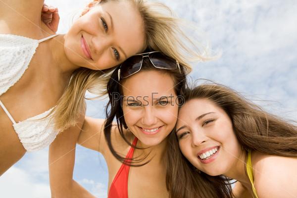 Фотография на тему Красивые молодые девушки обнявшись склонились к камере с улыбками
