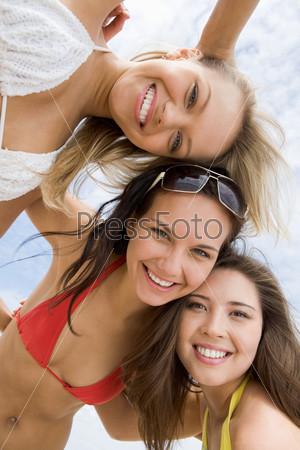 Очаровательные девушки в купальниках смотрят вниз в камеру и улыбаются