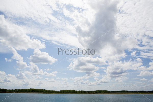 Белые облака плывущие над живописным озером