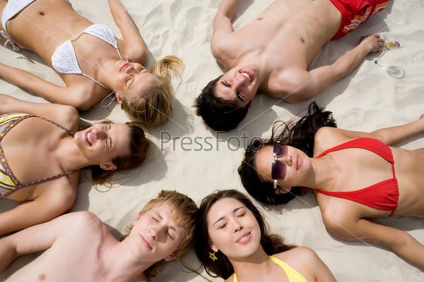 Компания друзей загорает на песчаном пляже