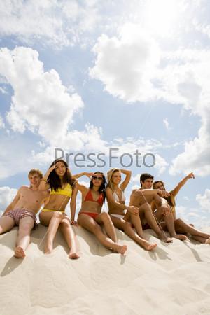 Шесть подростков сидят на песке и осматриваются вокруг