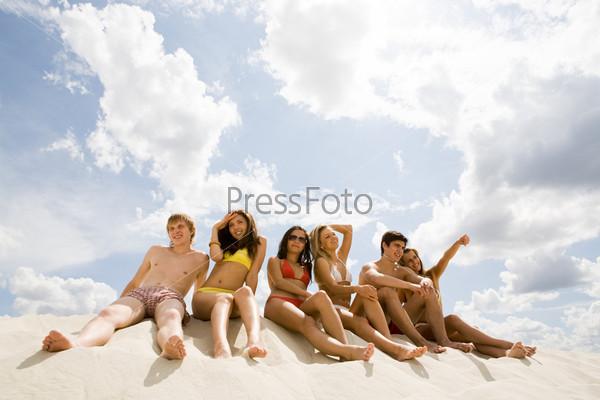 Фотография на тему Веселые молодые люди сидят на песке на фоне облачного неба