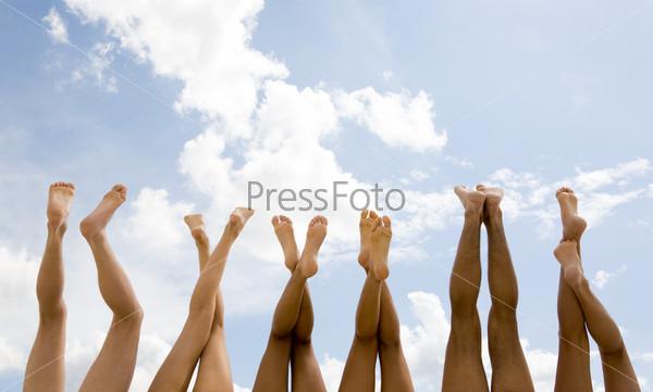 Шесть пар загорелых ног на фоне голубого неба