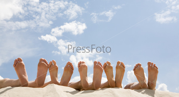 Ступни человеческих ног лежащие на песке на фоне неба