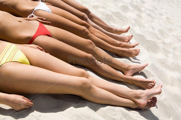 Линия стройных женских тел загорающих на песке