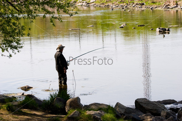 Рыболов с удочкой в руках на берегу реки в ветровке