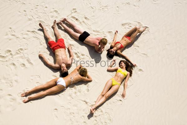 Вид сверху компании друзей загорающих на песчаном пляже