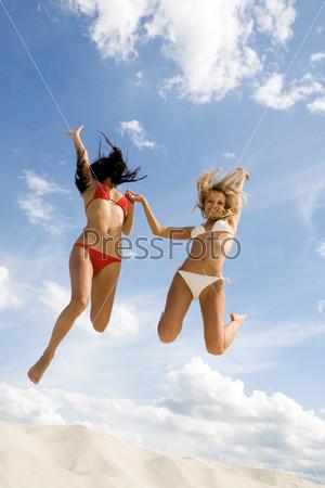 Две стройные подруги в купальниках в прыжке держатся за руки  на фоне неба