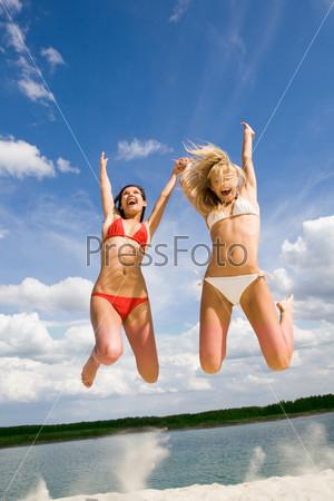 Две веселые подруги прыгают на песке на фоне живописного озера
