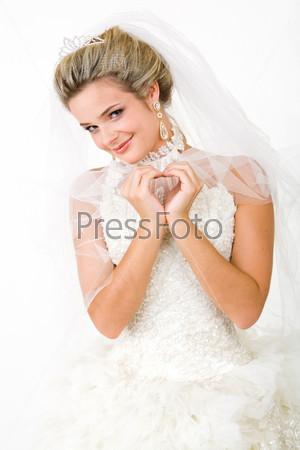 Молодая девушка в свадебном платье смотрит в камеру с улыбкой