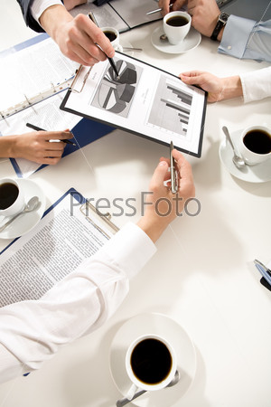 Руки бизнесменов над папкой с новым проектом