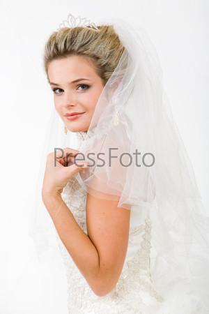 Изящная невеста в белом платье смотрит в камеру