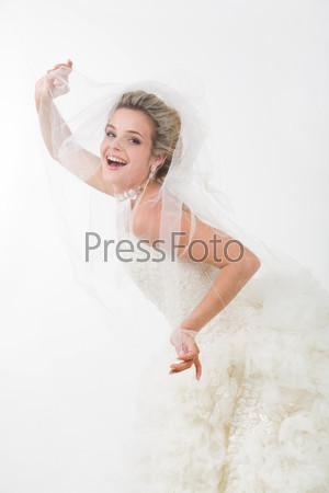 Роскошная невеста нагнувшись выглядывает из под вуали