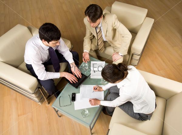 Успешные люди сидят на креслах и дискутируют