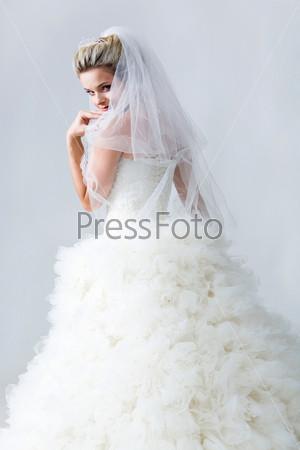 Красивая девушка в свадебном платье стоит вполоборота