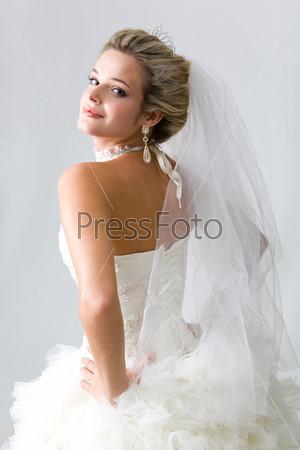 Уверенная в себе невеста стоит в свадебном наряде