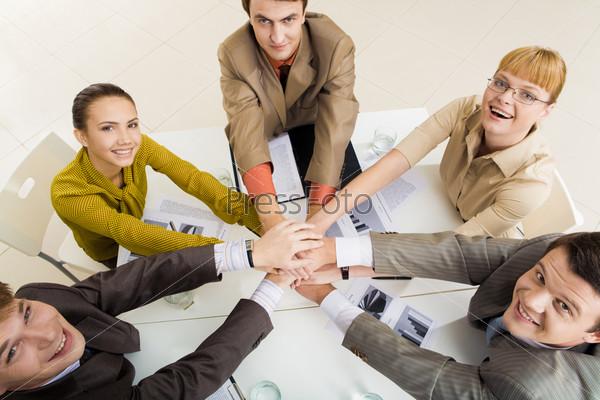 Деловые люди, сидя вокруг стола, изображают руками знак единства