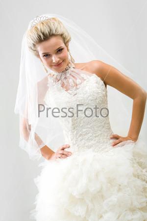 Шикраная невеста игриво смотрит в камеру и улыбается