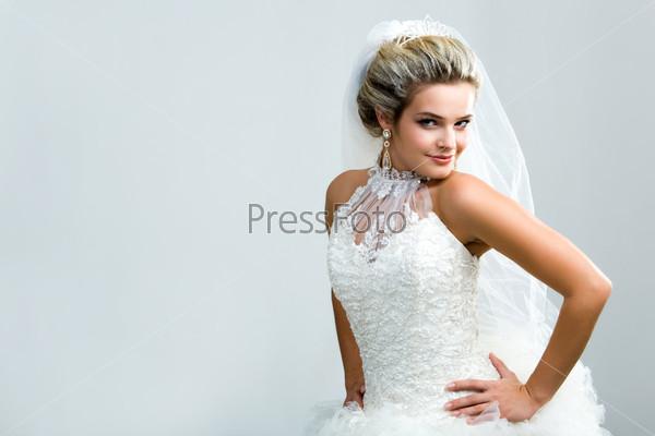 Очаровательная невеста позирует в камеру
