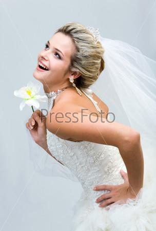 Смеющаяся невеста с орхидеей в руке