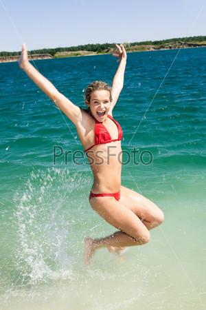Счастливая девушка  прыгает в воду