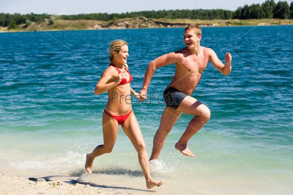 Молодая пара держится за руки и бежит по берегу
