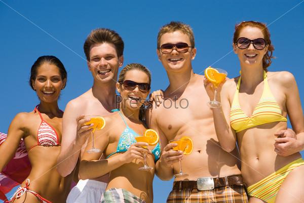 Счастливые подростки держат в руках коктели