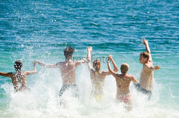 Молодые люди забегают с врызгами в воду