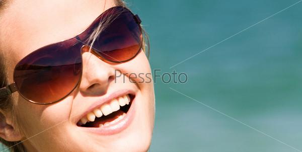 Девушка в темных очках смеется