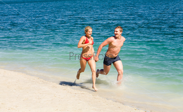 Парень с девушкой бегут по пляжу