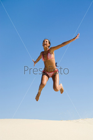 Portrait of joyful girl leaping on sandy beach during summer vacation and laughing