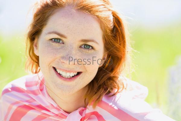 Молодая рыжеволосая девушка смотрит в камеру
