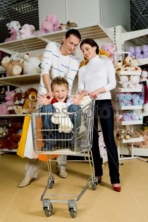 Муж с женой смотрят на сына в отделе игрушек
