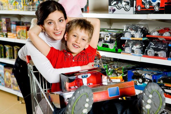 Женщина обнимает сына в магазине игрушек