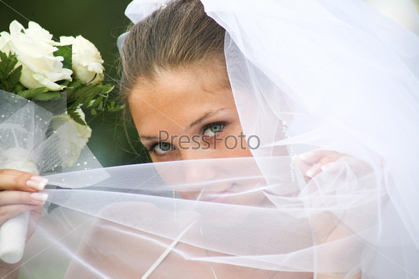Крупный план очаровательной невесты в фате, держащей в руках букет