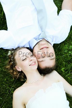 Фотография на тему Влюбленные молодожены лежат на траве прикрыв глаза
