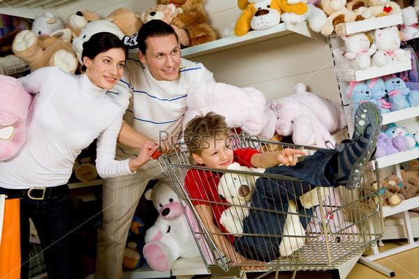 Ребенок показывет что-то родителям в магазине