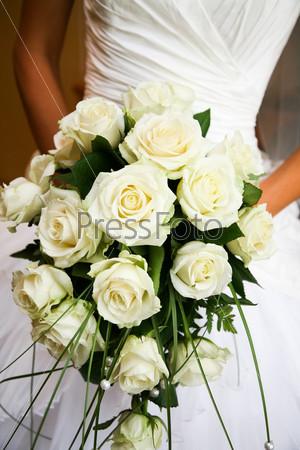 Крупный план свадебного букета из белых роз в руках невесты