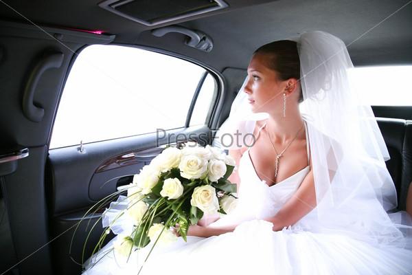 Красивая невеста едет в машине глядя в окно