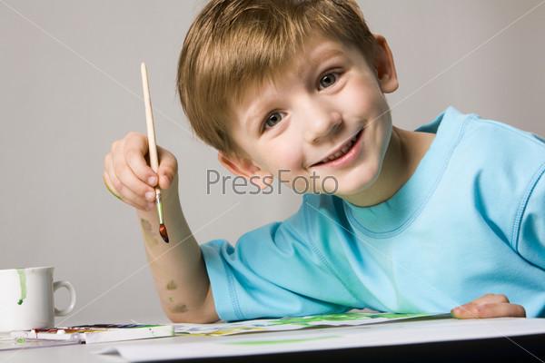 Мальчик с улыбкой на лице сидит за столом и держит в руке кисть