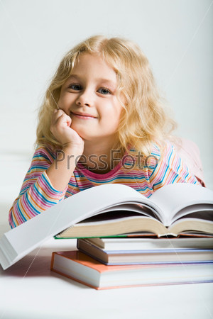 Школьница лежит среди книг и улыбается на белом фоне
