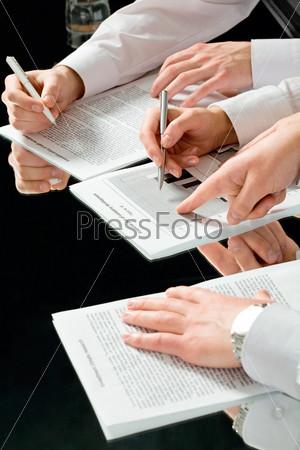 Руки бизнесменов за столом держащие ручки