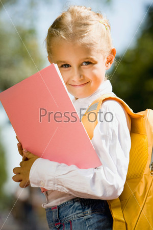 Portrait of smiling adorable girl with backpack holding a book outside