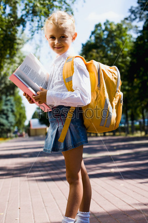 Первоклассница с рюкзаком на спине держит книгу