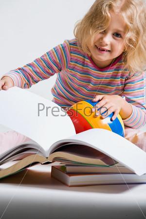 Маленькая девочка сидит перед книгами и держит мячик