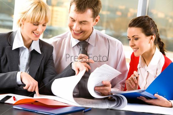 Деловые люди просматривают бумаги сидя за столом