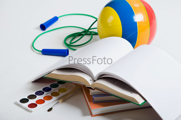 Кники, мячик, краски и скакалка на белом фоне